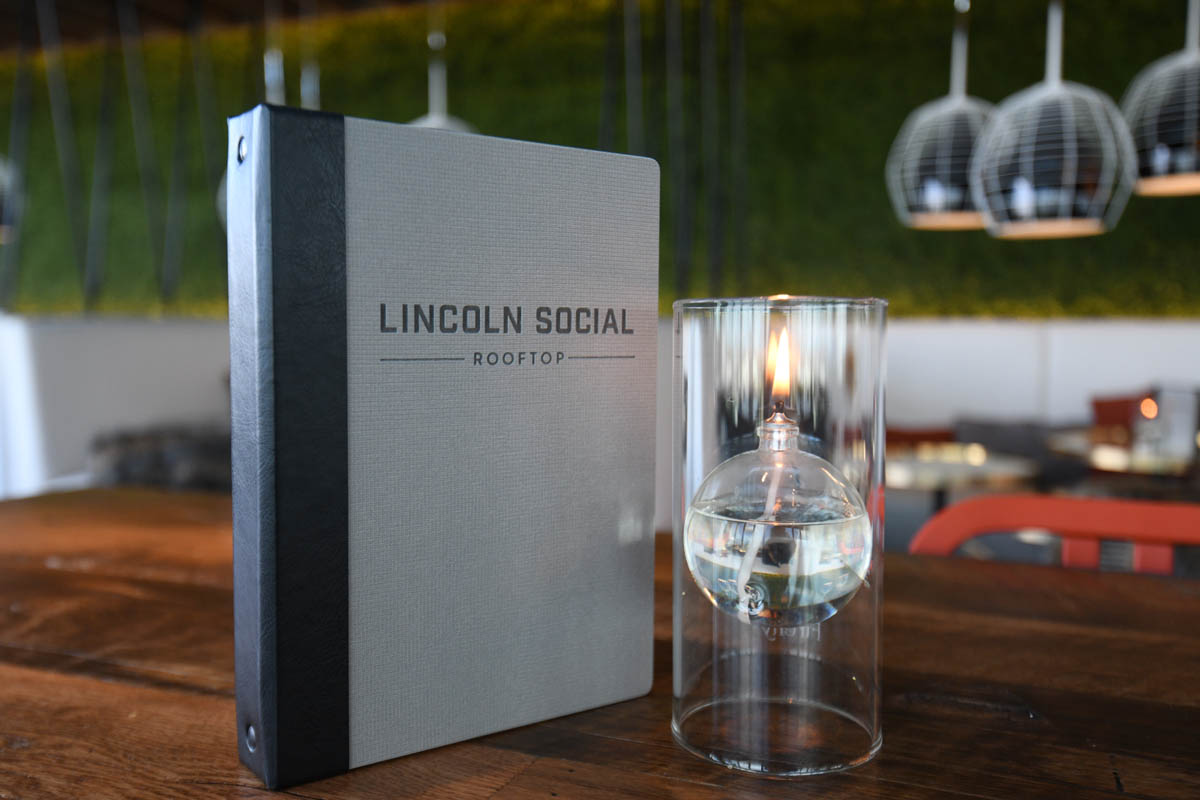 Lincoln Social menu book and candle