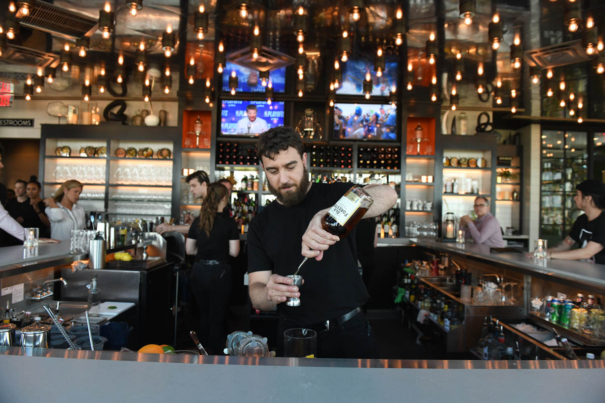 Lincoln Social bartender pouring cocktail