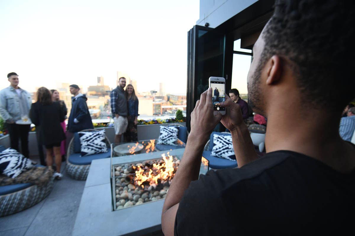 Lincoln Social guests and associate taking a photo by firepit and view