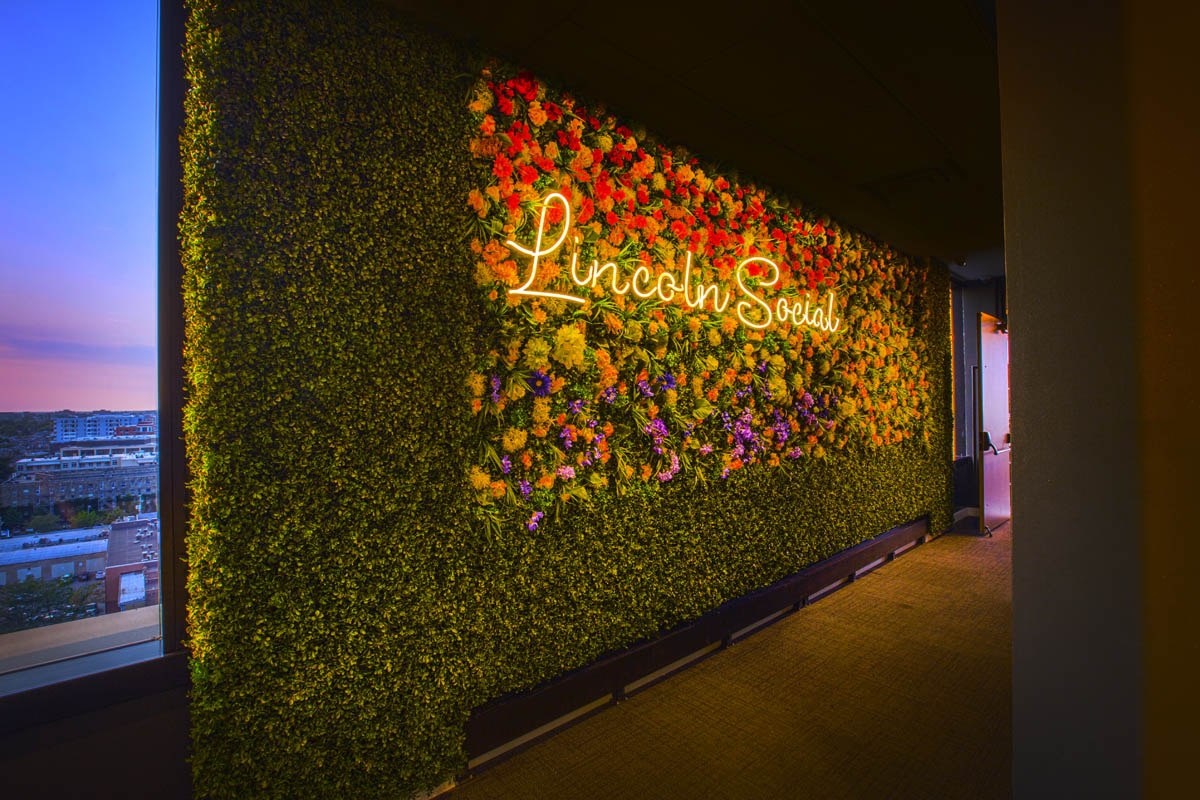 Interior Lincoln Social entrance with flower wall and logo sign