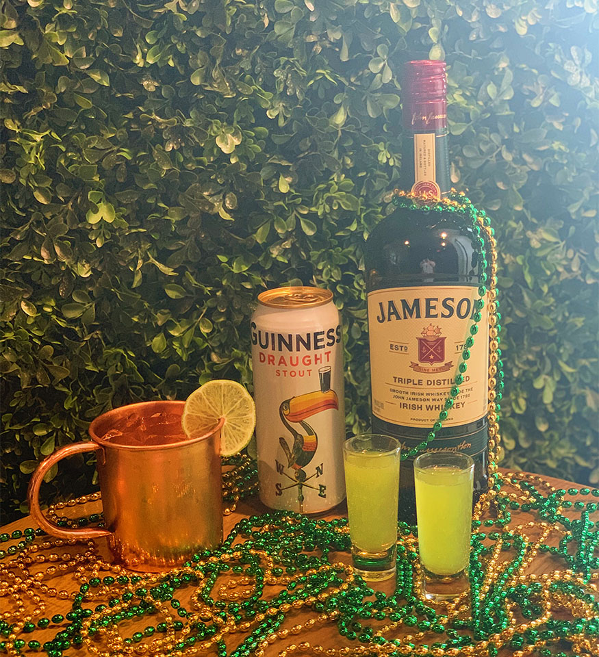 Bottle of Jameson and a can of Guinness on a table with green and gold Mardi Gras beads, two bright green shots in shot glasses, and a Moscow Mule with a lime garnish.