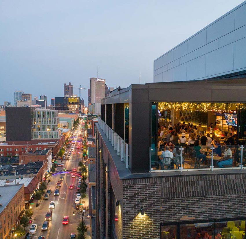 Drone view of Lincoln Social rooftop lounge with guests, facing Downtown Columbus showing High Street traffic below