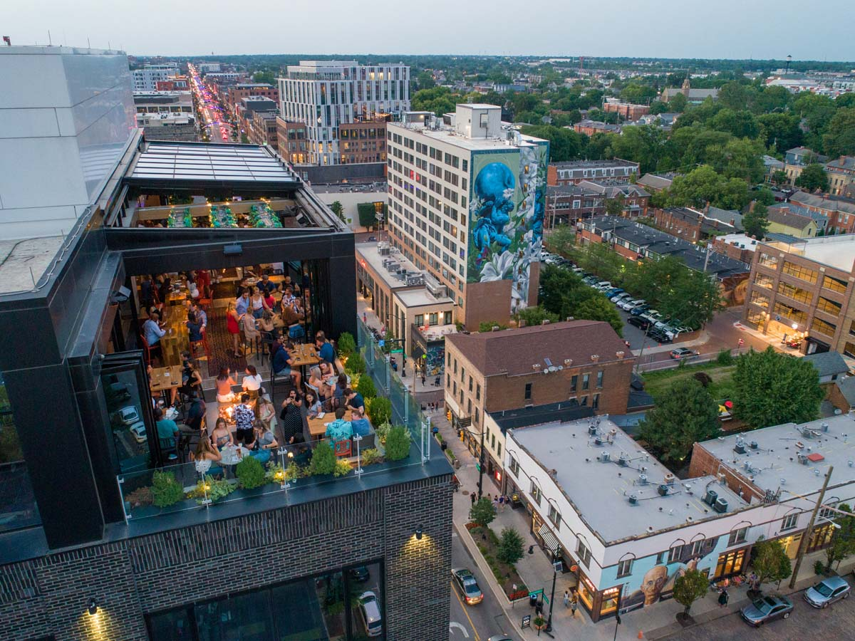 Drone view of dusk on Lincoln Social rooftop facing downward to High Street below
