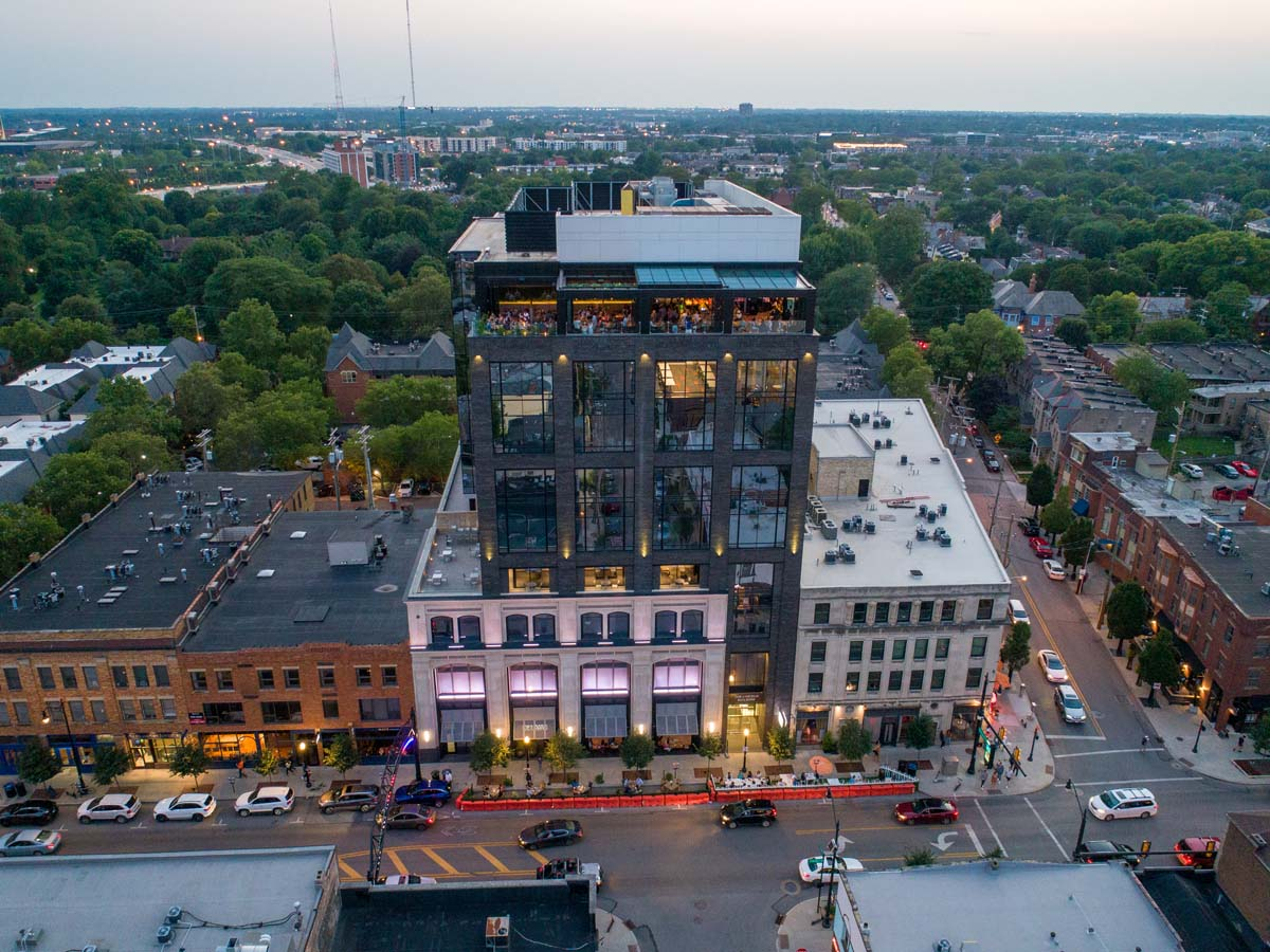 Drone view of dusk on Lincoln Social rooftop with view of full building below