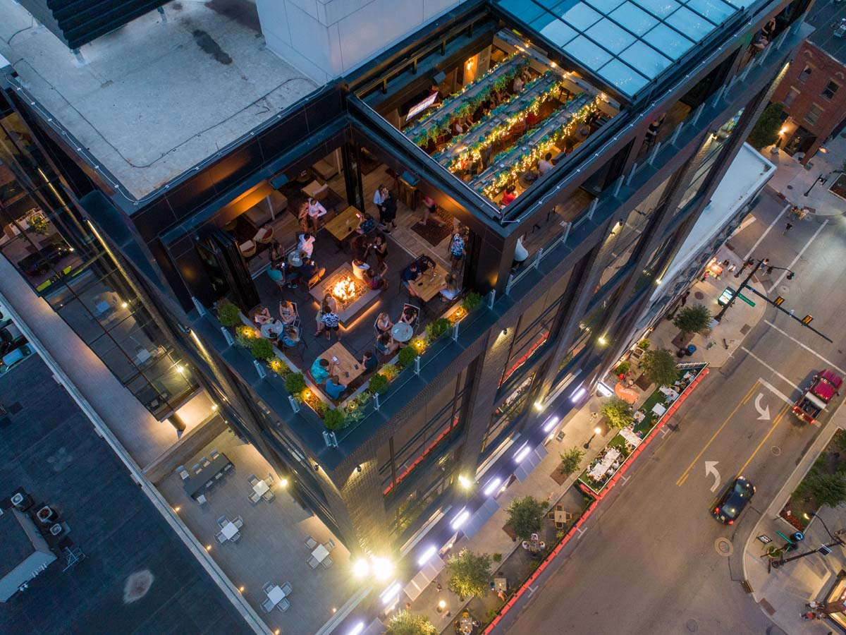 Drone view of dusk on Lincoln Social rooftop facing downward over bar with view to sidewalk below