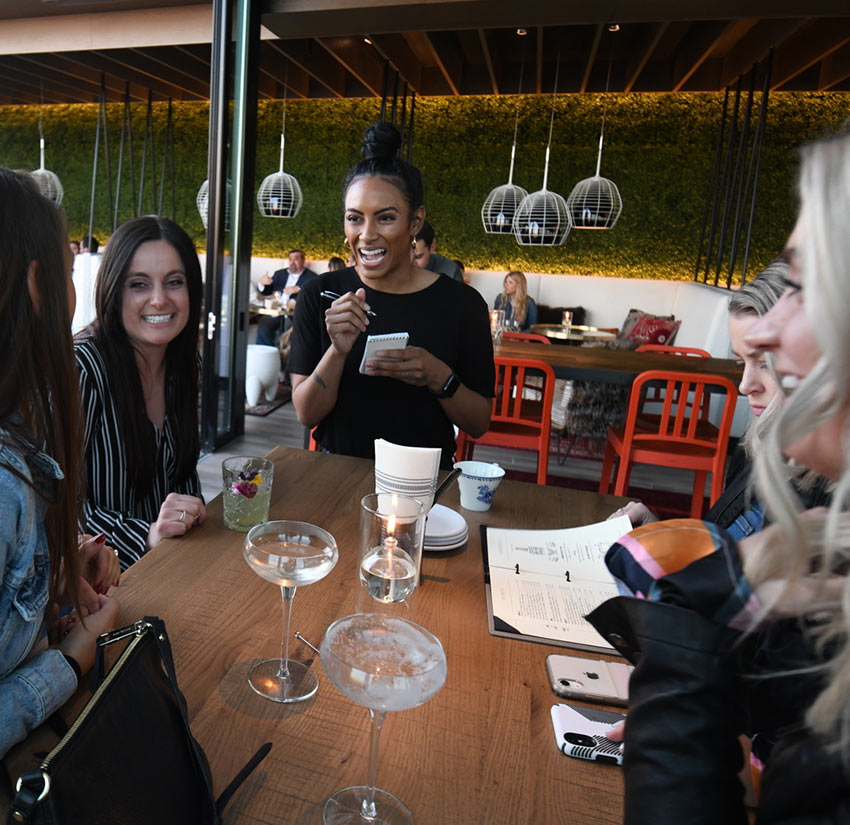 table of guests seated with drinks laughing with server